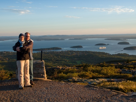 Couple at sunrise over the sea on top of Cadillac Mountain in Acadia National Park photo