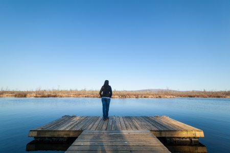 Woman standing on a wooden deck besides a lake