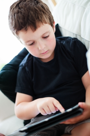 Boy playing on a tablet while sitting on a couch Stock Photo