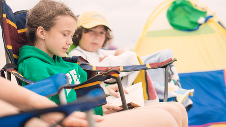 Young girl reading in a chair on the beach while is brother is watching photo