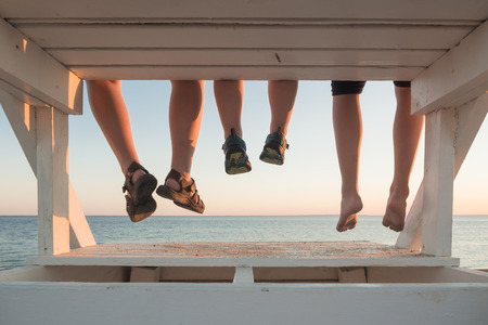Family with their feet hanging at sunset in Cape Cod Stock Photo