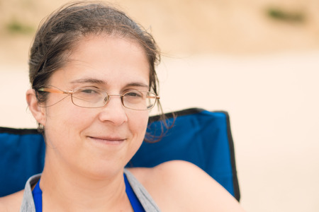 Woman smiling and sitting in a chair on the beach Stock Photo
