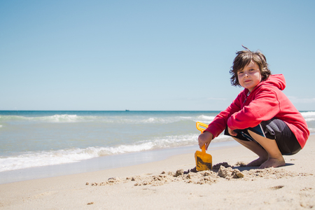 Boy playing in the sand on the beach in Cape Cod Stock Photo