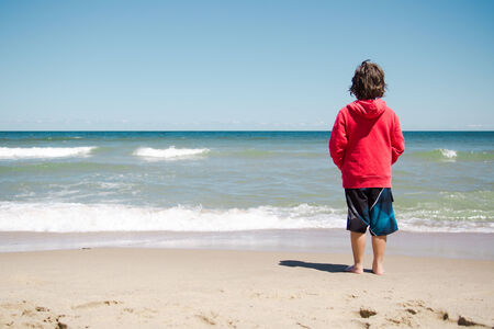 Boy standing on the beach and relaxing in Cape Cod photo