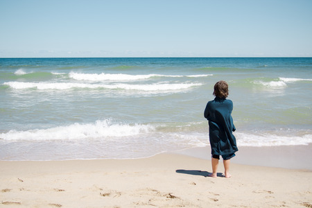 Boy standing on the beach and relaxing in Cape Cod