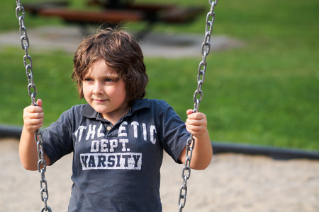 Boy sitting on a swing in a playground photo