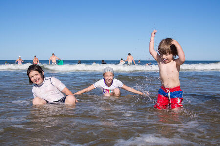 Kids playing in the water at the sea Stock Photo