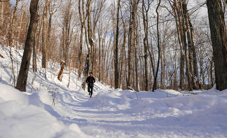 Man trail running in the snow on a beautiful winter day Stock Photo