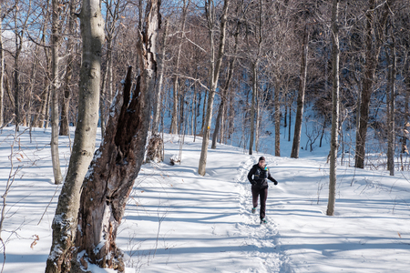 Woman running in the snow on a trail in the woods