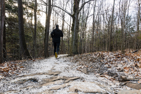 Man running in the snow on a trail in the woods Stock Photo