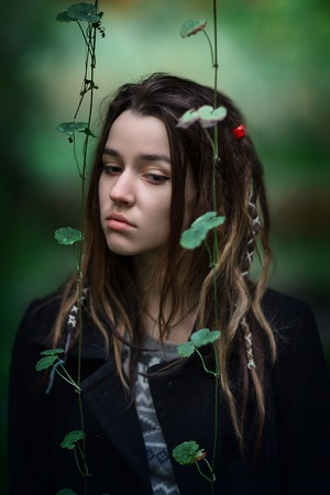 liana: The young beautiful girl looks down. The girl carries dreadlocks. On a foreground liana leaves hang down. Stock Photo