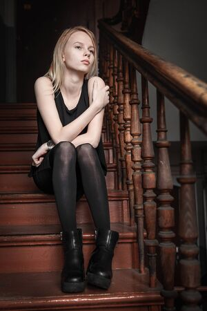misses: The girl grieves, misses. The girl in a black dress sits on steps. The girl the blonde dreams.