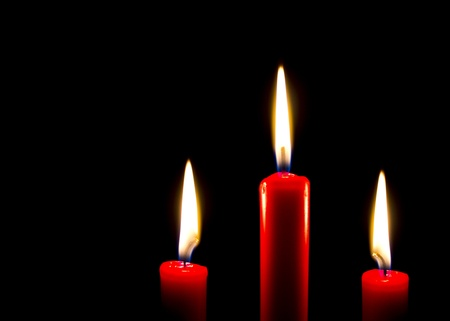 Three red burning candles on a black background Stock Photo