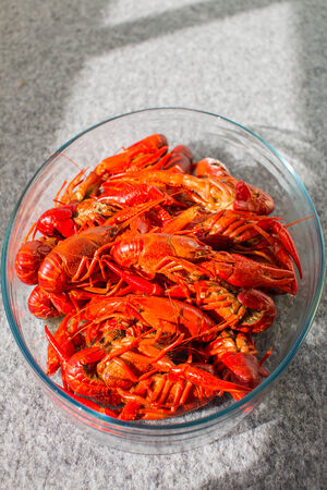 Red boiled crawfish in clear glass bowl