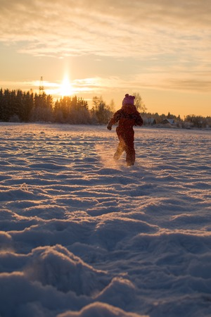 Child runs to meet the sun in winter photo