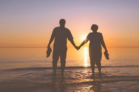 Happy senior couple silhouettes on the beach Banque d'images