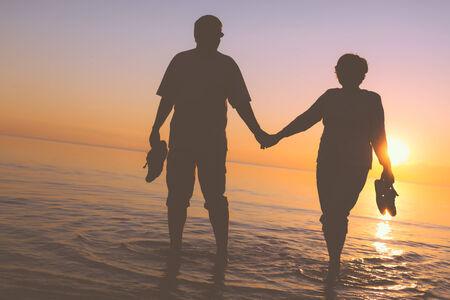 Happy senior couple silhouettes on the beach Stock Photo