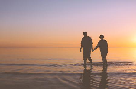 parejas caminando: Pares mayores que recorren en la puesta del sol Foto de archivo