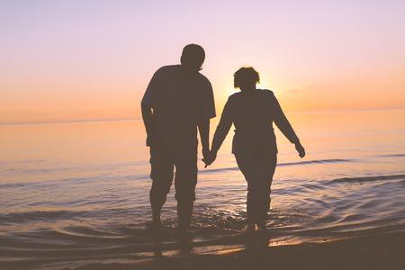 Senior couple walking at sunset photo