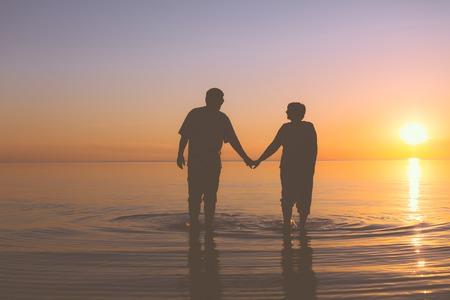 Senior couple walking holding hands at sunset Stock Photo