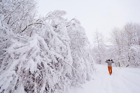 ax man: Lumberjack walks in a snowy forest