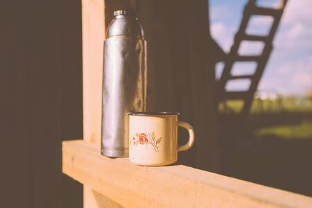 thermos: Thermos and a mug on a construction site