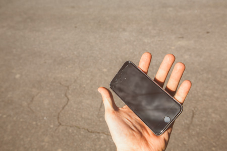 portable failure: Smartphone with broken screen in hand. cracked screen.