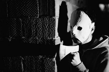 maniac: Maniac with an ax to expect the victim near a brick wall. Black and white photo close-up.