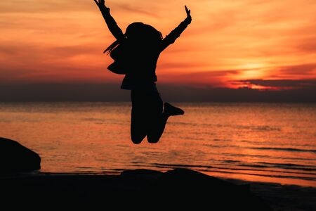 Happy girl jumping against beautiful sunset. Freedom, enjoyment concept.