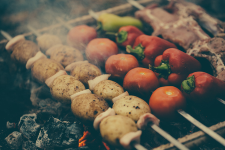 Meat and vegetables are roasted on coals. Bell pepper, potato, tomato and meat
