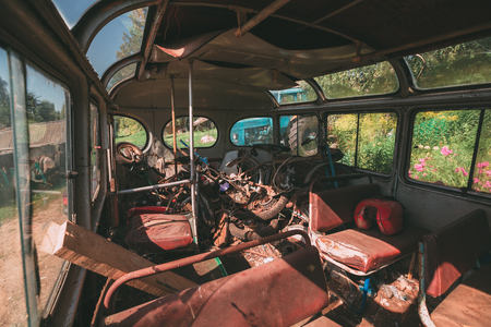 cushioned: Old rusty bus in a lot of rusty metal and trash inside view.