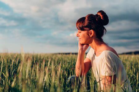 Hermosa chica morena con los ojos cerrados, sentado en un campo. Foto de archivo