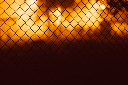 chain fence: Mesh fence close-up on a blurred background of orange and brown.