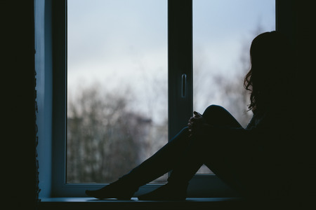 sexually: Young woman sexually sits on a window sill. Black and white photo closeup. Stock Photo