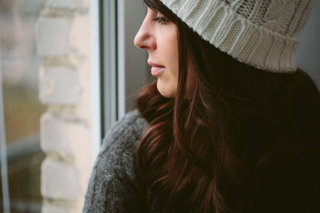 dream: Girl in a cap looks out of the window closeup photo. Stock Photo