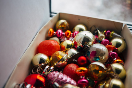 Closeup view of many beautiful christmas or new year fir tree decoration colorful toys in box.