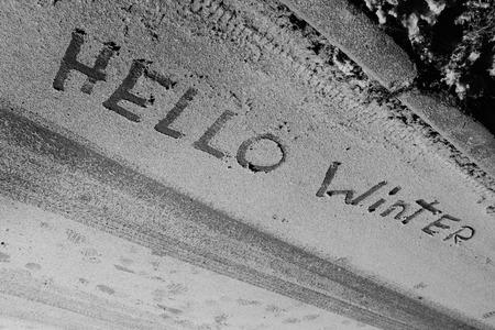 Inscription on the snow hello winter close up photo.