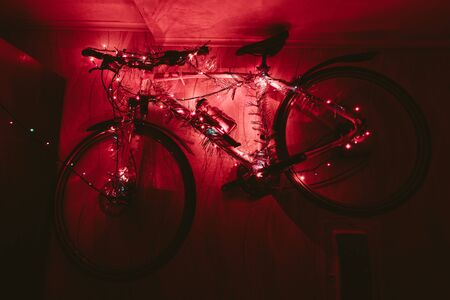 goodly: Bicycle on a wall decoration of the christmas lamp garland in the dark close up photo.