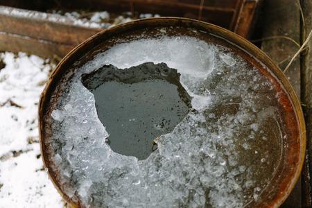 ferruginous: Broken ice in an old rusty barrel closeup photo. Stock Photo