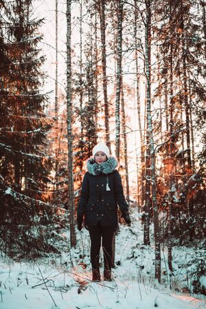 girl in full growth: Pretty girl in a white hat and a jacket on a background of a winter forest. Photo girl in full growth.