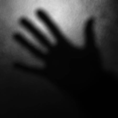 terribly: Abstract blurred black and white background with one hand. Stock Photo