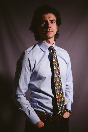stubbly: Casual young man businessman in a shirt and with a tie on a dark background.