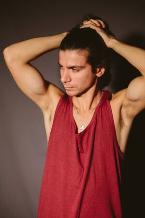 undershirt: Young man the athlete in a red undershirt and hands behind the head on a dark background. Stock Photo