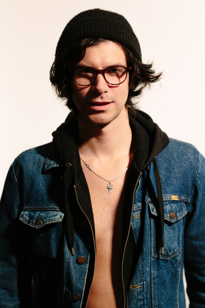 unbuttoned: Modern fashionable young man in glasses and unbuttoned jacket.