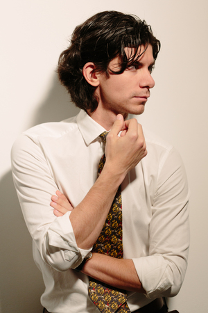 stubbly: Young man in a white shirt and tie holding his chin thinking. Photo on a white background.