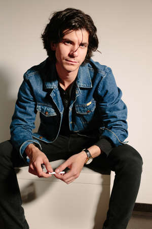 Young man in a jeans jacket holds a cigarette in hand and sits on the ottoman. Stock Photo