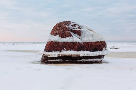 winter time: Big stone in winter time against the sky and the gulf. Stock Photo