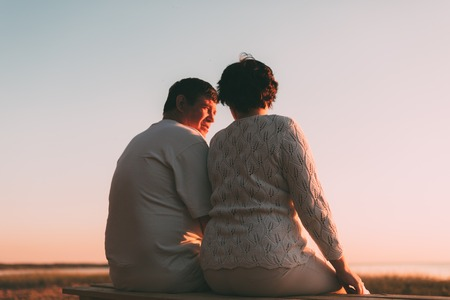 pareja de esposos: Vista posterior de una pareja casada una silueta sentada en un banco. la noche foto.