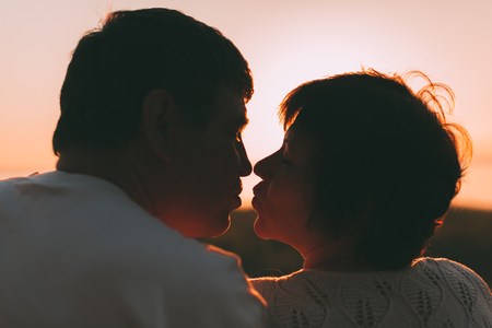 each: Adult married couple last to each other to kiss. Photo against a sunset. Stock Photo