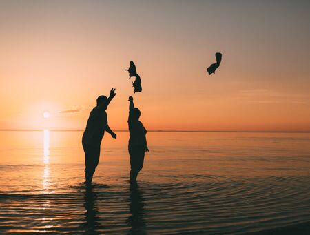 beack: Couple of man and woman standing in the sea and throw your shoes at the beach. Photo against a sunset. Stock Photo